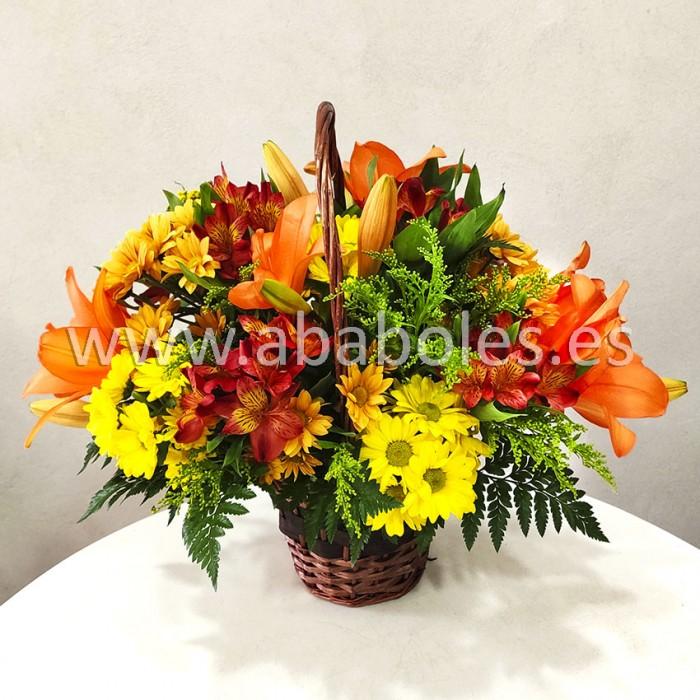 Cesta de flores en tonos cálidos