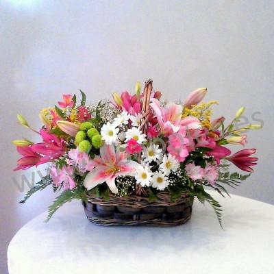Cesta de flores en tonos rosa y blanco