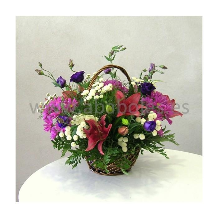Cesta de flores en tonos rosa y morado.